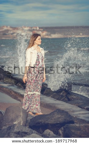 Girl in summer  dress standing on beach and looking to the sea - stock photo