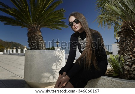 Girl in sunglasses and posing next to a beautiful ornament on the background of palm trees. Style, fashion, beauty.