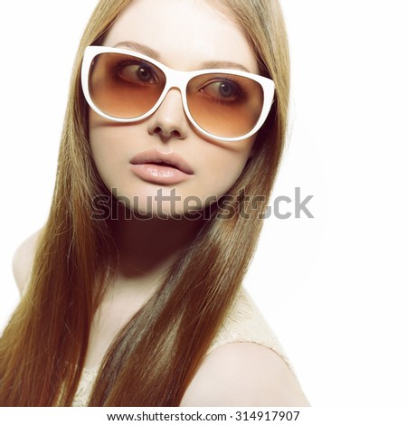Girl in sunglasses. Beautiful woman in sunglasses posing in studio over white background.