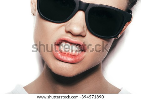 Girl in sunglasses. Beautiful woman in sunglasses posing in studio over white background not isolated - stock photo
