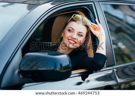 Girl in sunglasses drive a car and look from window