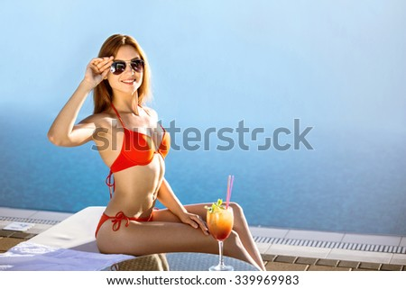 Girl in sunglasses resting on the beach. She is smiling and enjoying summer rest