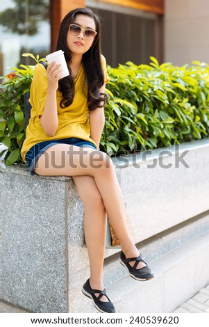 Girl in sunglasses sitting outdoors and drinking coffee - stock photo