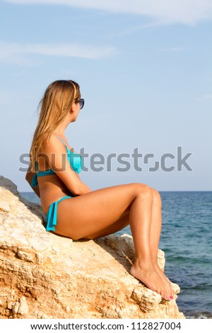 Girl in swimsuit near the sea sitting on the big stone - stock photo