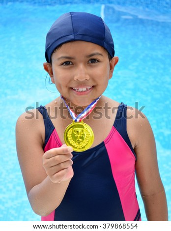 Girl in swimsuit with medals in swimming pool. - stock photo
