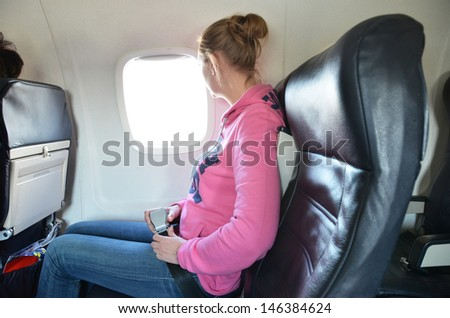Girl in the airplane - stock photo