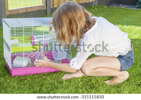 Girl in the backyard playing with the hamster in cage - stock photo