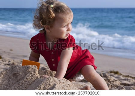 Girl in the beach, looking at the sea - stock photo