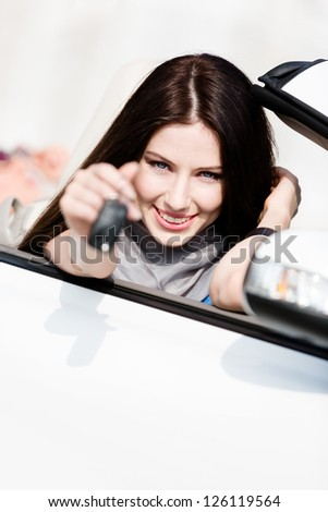 Girl in the cabriolet shows car key. Buying car and getting the freedom - stock photo