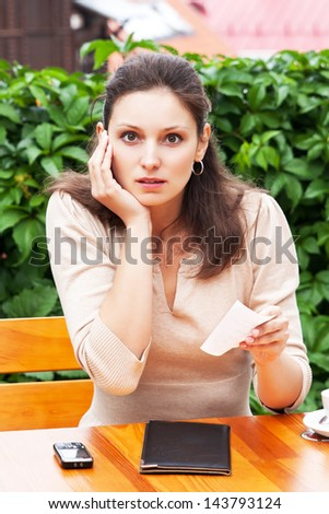 Girl in the Cafe is shocked by the bill - stock photo