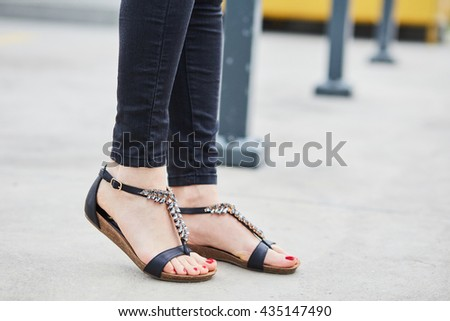 Girl in the city wearing dark jeans and black sandals, space for text - stock photo
