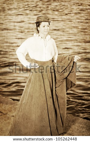 Girl in the clothes in the retro style near the river Neva in St.Petesburg, Russia. Vintage style, grungy effect, sepia tint. - stock photo