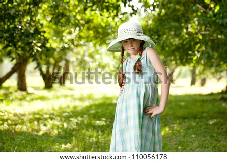 Girl in the hat and dress of apple orchard