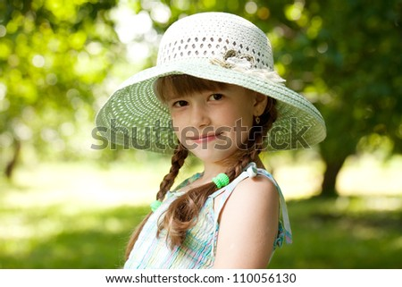 Girl in the hat and dress of the garden trees