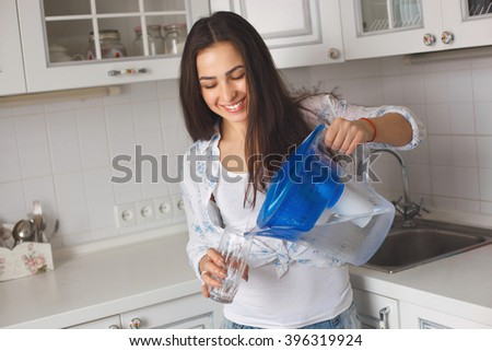 girl in the kitchen pouring water from the filter