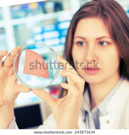 girl in the laboratory of food quality tests sausage - stock photo