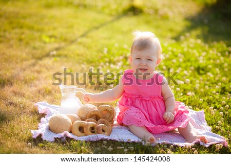 Girl in the meadow with milk and buns - stock photo