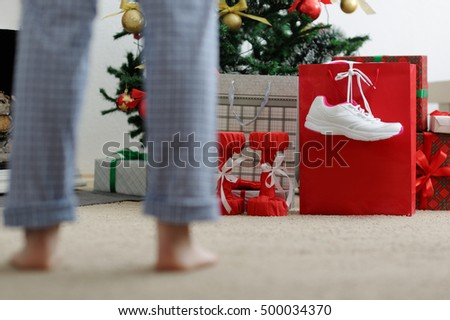 Girl in the morning looking for Christmas gifts. Athletic shoes for running, dumbbells fitness.