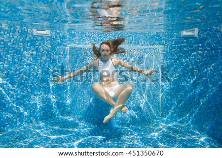 girl in the pool. She dives into the pool. Under water in a white bathing suit