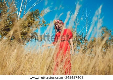 Girl in the Red Dress Walking on the Field - stock photo