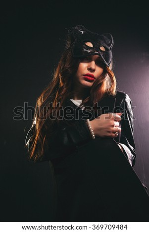 Girl in the studio posing for the camera in a cat mask with red lips.