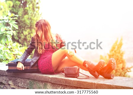 Girl in the sun on a wall with suitcase