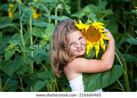 Girl in the sunflowers field with a sunflower - stock photo