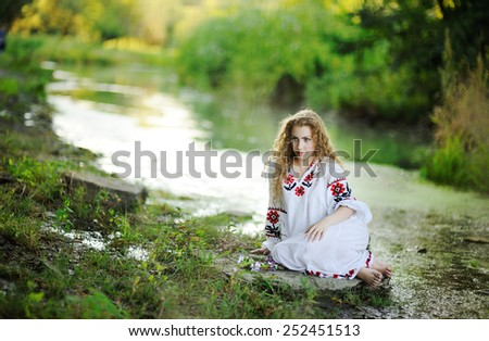 girl in the Ukrainian national clothes with wreaths of flowers on the riverbank