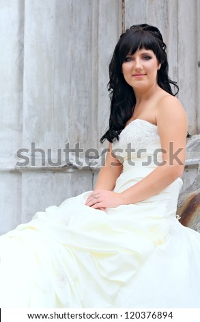 Girl in the wedding dress sitting at a stones