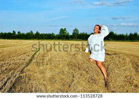 girl in traditional Russian costume sitting on a haystack and smiling, space for text - stock photo