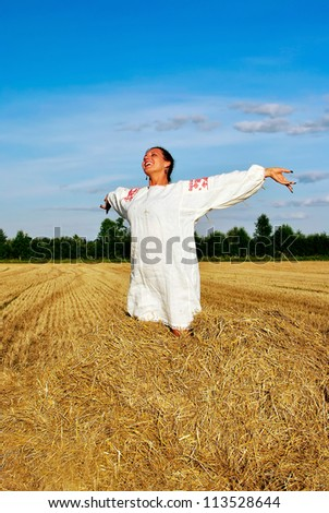 girl in traditional Russian costume sitting on a haystack, space for text - stock photo