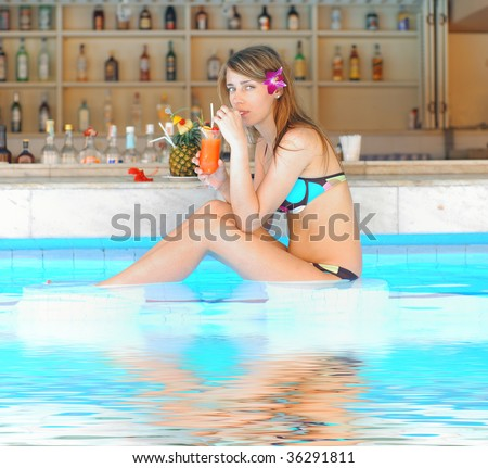 Girl in tropical pool bar with cocktail. Reflection in water. - stock photo