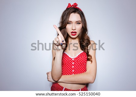 Girl in underwear shows finger in studio. looking at camera. serious girl. isolated gray background