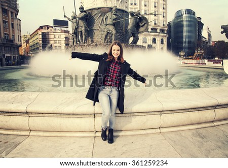 Girl in urban city. Fountain behind her. Retro colors