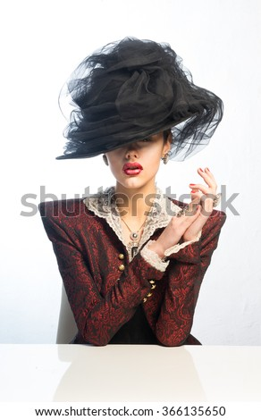 Girl in vintage hat sits at the table - stock photo