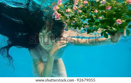 Girl in water with flowers - stock photo