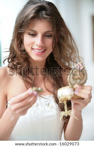 girl in wedding gown looks at gift from beautiful box and rejoices - stock photo