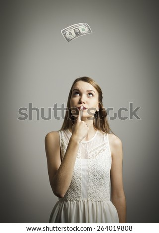Girl in white and falling dollar banknote. Currency and lottery concept.