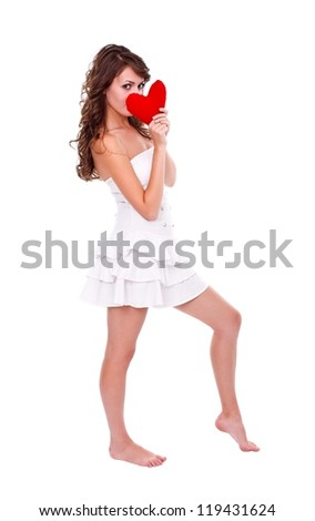 Girl in white clothes holding red heart in front of her face - stock photo