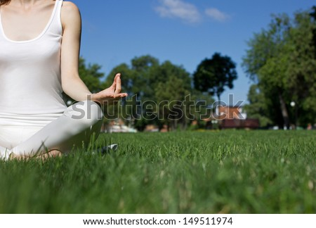 girl in white clothes siting in yoga pose on green grass in park, closeup - stock photo