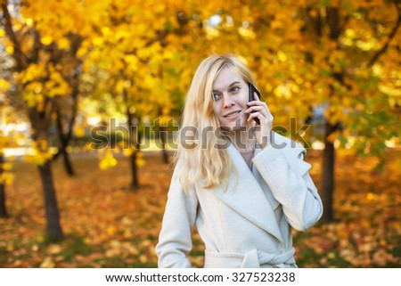 girl in white coat talking on the phone in the autumn park