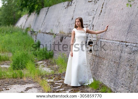 girl in white dress at the concrete wall - stock photo