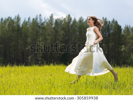 girl in white dress jumping in a field - stock photo
