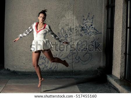 Girl in white dress jumps before the grey wall on the street