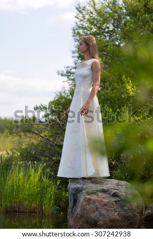 girl in white dress on the lake in the green against the sky stands on a stone - stock photo
