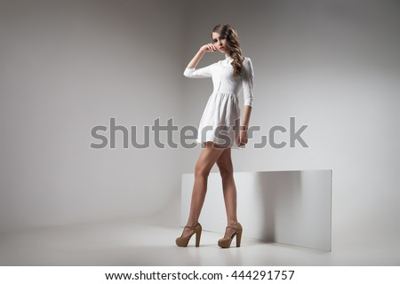 Girl in white dress posing against of grey