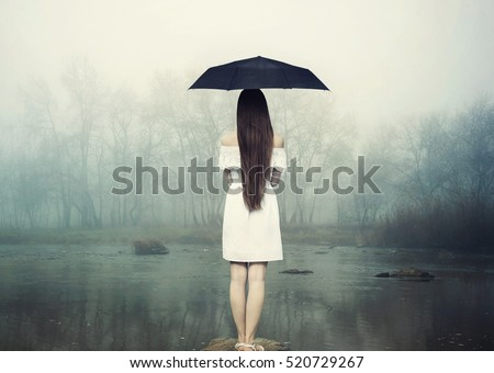 Girl in white dress with umbrella. Woman standing on the stone at the  river