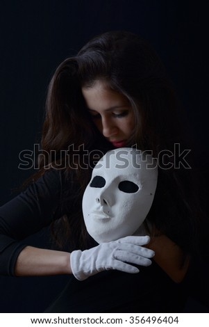 girl in white gloves holds a theatrical mask near the face
