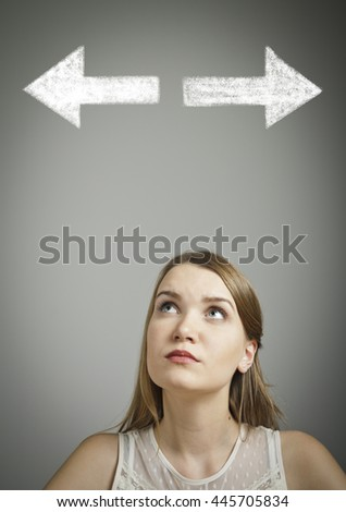 Girl in white has to decide between two directions. Girl in white full of doubts and hesitation. - stock photo