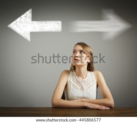 Girl in white has to decide between two directions. Girl in white full of doubts and hesitation.